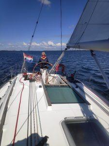 juf Anja achter het stuur van een grote zeilboot