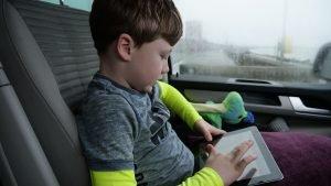 foto van jongen achterin de auto met Ipad